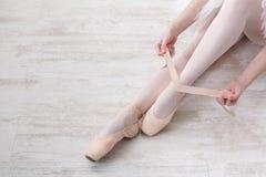 Балерина кладет дальше ботинки балета pointe, грациозно ноги Стоковые Изображения