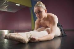 Балерина сидя и гнуть вперед стоковые изображения