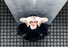 Балерина смотря вверх против плиток серого цвета и Стоковые Изображения