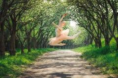 Балерина танцуя outdoors и скача высоко в воздух Стоковая Фотография