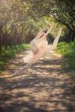 Балерина танцуя outdoors и скача высоко в воздух Стоковое Фото