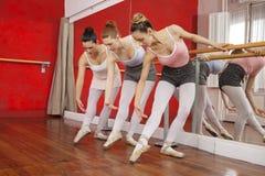 Балерины гнуть пока выполняющ в тренируя студии Стоковые Изображения