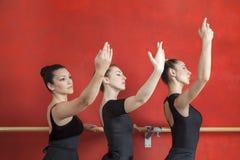 Балерины практикуя на Barre балета против красной стены Стоковые Изображения