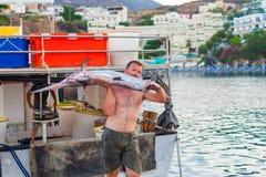Бали, остров Крит, Греция, - 30-ое июня 2016: Человек рыболов носит больших пилорылых рыб Стоковое Фото