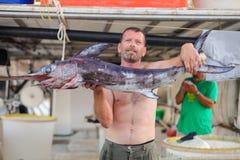Бали, остров Крит, Греция, - 30-ое июня 2016: Человек рыболов носит больших пилорылых рыб Стоковые Фотографии RF
