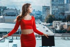 Балкон девушки стоящий, на предпосылке большого города Стоковая Фотография
