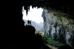 Ба озера/Вьетнам, 03/11/2017: Силуэты 2 людей стоя в скалистом выходе на поверхность внутри гигантской пещеры на севере стоковые фотографии rf