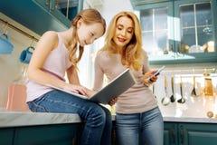Бдительные мать и девушка используя современные приборы Стоковая Фотография