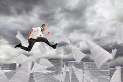 Бега бизнесмена далеко от рабочих листов и канцелярщины стоковая фотография rf