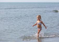 Бега девушки вдоль пляжа Стоковые Изображения