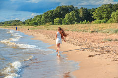Бега девушки вдоль seashore Стоковое Изображение