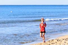 Бега девушки вдоль seashore Стоковое Фото