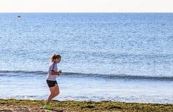 Бега девушки вдоль seashore Стоковая Фотография RF