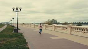Бега девушки спорт вдоль бульвара видеоматериал