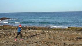 Бега женщины вдоль каменистого берега океана Здоровый активный образ жизни сток-видео