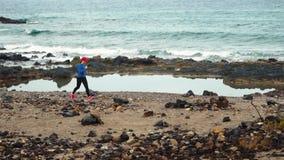Бега женщины вдоль каменистого берега океана Здоровый активный образ жизни ( акции видеоматериалы