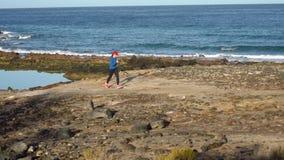 Бега женщины вдоль каменистого берега океана Здоровый активный образ жизни акции видеоматериалы