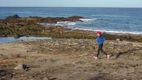 Бега женщины вдоль каменистого берега океана Здоровый активный образ жизни видеоматериал
