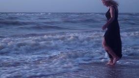 Бега женщины далеко от волн, пены моря, на пляже в ветреной погоде видеоматериал