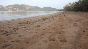 Бега маленькой девочки вдоль пляжа на восходе солнца