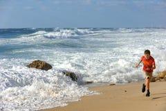 Бега мальчика вдоль берега Стоковая Фотография