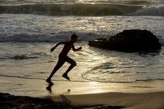 Бега мальчика вдоль берега Стоковые Фото