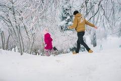 Бега папы для его дочери в зиме стоковое изображение rf