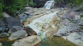 Бега потока близкого взгляда трутня вдоль скалистой поверхности в озеро