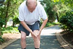 бегунка боли колена ушиба спорты мыжского идущие Стоковое фото RF