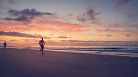 Бегуны бегут на пляже на восходе солнца Стоковое Изображение RF