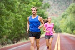 Бегуны - марафон тренировки пар идущий на дороге Стоковые Фотографии RF