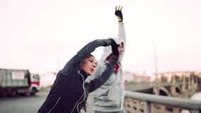 Бегуны подходящие пары делая протягивать outdoors на мосте в городе Праги сток-видео
