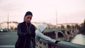 Бегуны подходящие пары делая тренировку outdoors на мосте в городе Праги сток-видео