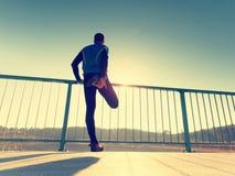 Бегун в черных гетры делает тело протягивая на пути моста Солнце конспектирует тело человека Стоковое Фото