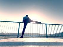 Бегун в черных гетры делает тело протягивая на пути моста Солнце конспектирует тело человека Стоковое Изображение