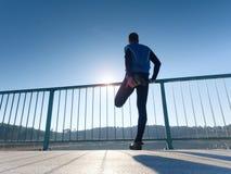 Бегун в черных гетры делает тело протягивая на пути моста Солнце конспектирует тело человека Стоковые Фото