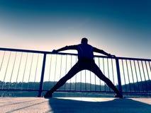 Бегун в черных гетры делает тело протягивая на пути моста Солнце конспектирует тело человека Стоковое фото RF
