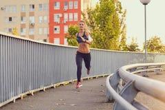 Бегун девушки бежит на мосте в городе в лете осени Стоковые Изображения