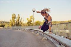 Бегун девушки скачет над перилами на мосте в городе Стоковое Изображение