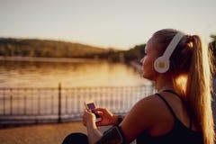 Бегун девушки сидя в парке слушая к музыке Стоковое Фото