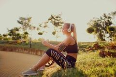 Бегун девушки слушая к музыке в парке Стоковое Изображение