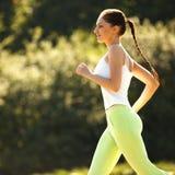 Бегун женщины. Девушка фитнеса бежать outdoors Стоковые Изображения RF