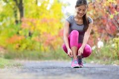 Бегун женщины идущих ботинок связывая шнурок ботинка для бега Стоковая Фотография RF