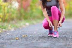 Бегун женщины идущих ботинок связывая шнурок ботинка для бега Стоковые Фотографии RF