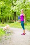 Бегун женщины идя с собакой в парке лета стоковая фотография rf