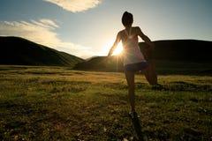 бегун женщины нагревая на следе злаковика захода солнца Стоковая Фотография
