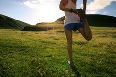 бегун женщины нагревая на следе злаковика захода солнца Стоковое Изображение RF
