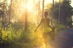 Бегун женщины нагревая на следе леса восхода солнца Стоковое Фото