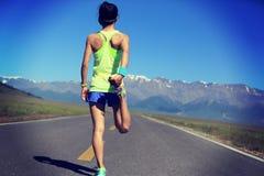 Бегун женщины протягивая ноги на горной тропе Стоковое Изображение RF