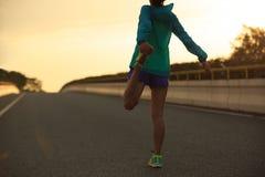 Бегун женщины протягивая ноги на дороге города Стоковое фото RF